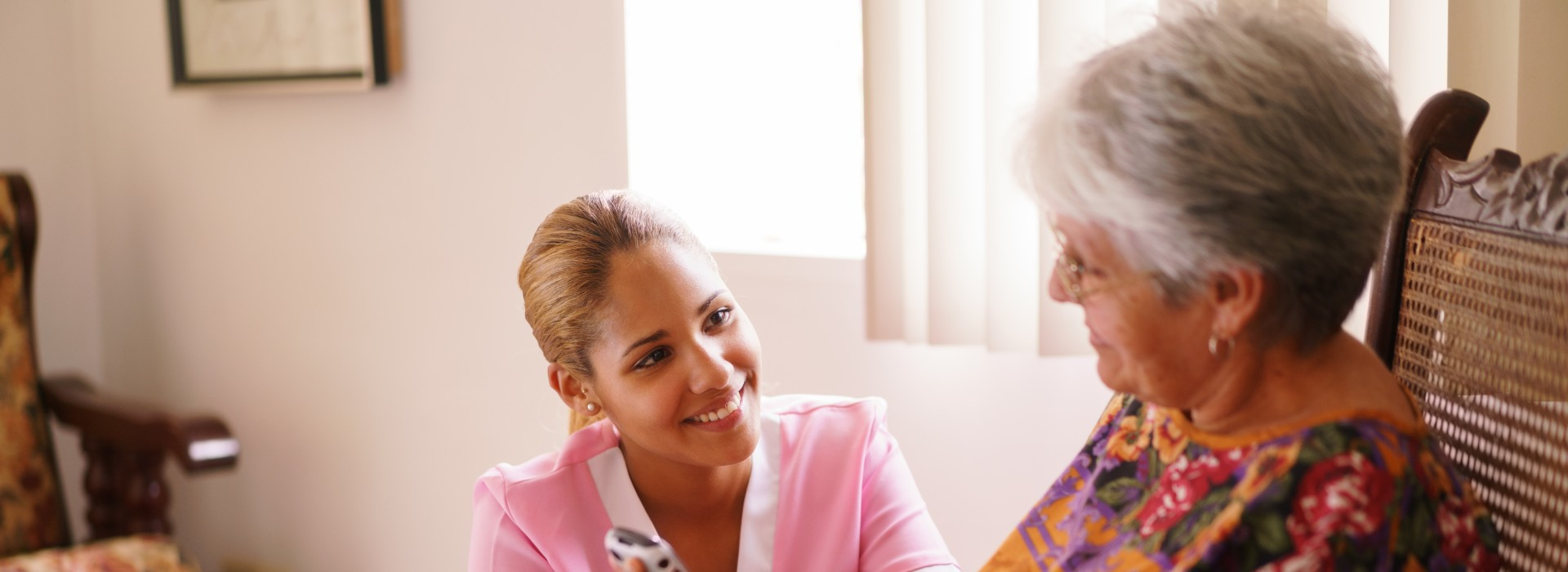 young nurse comforting elderly woman in home health care Gracia Hospice